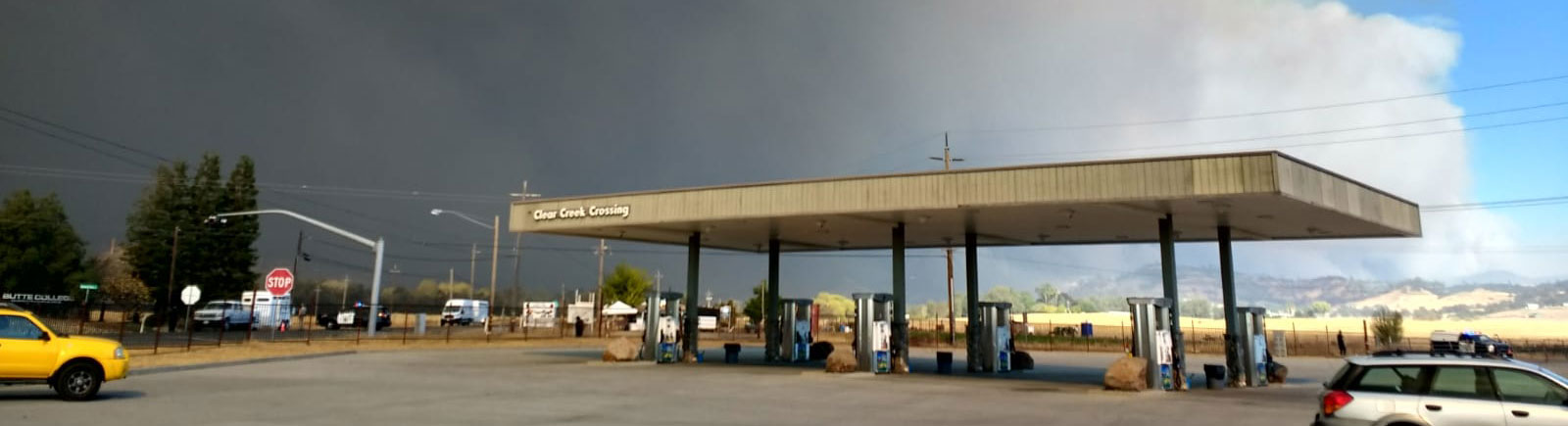 gas station with smoke from a fire in the background