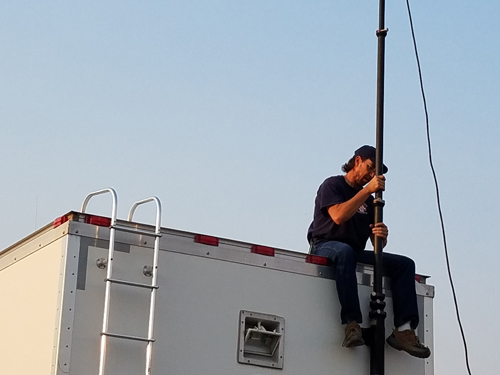 volunteer attaching antenna to rescue trailer